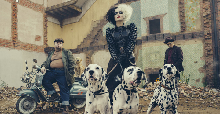 Cruella Holding Three Dalmation Dogs, Two People In Background.