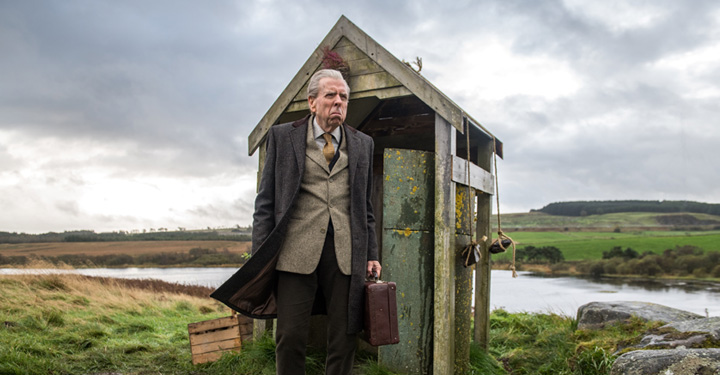 Man Stood Outside A Wooden Hut In Country Side.