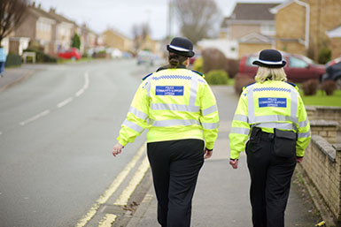 Two Police Persons On A Street.