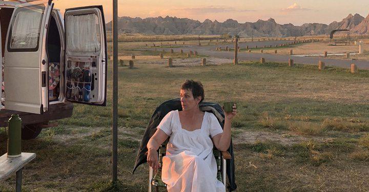 Frances Mcdormand Sat Outside A Campervan.
